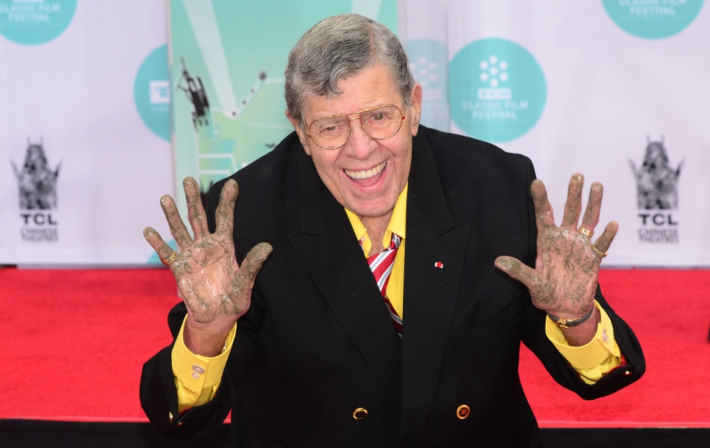 Jerry Lewis shows his hands after immortalizing his handprints and footprints at the TCL Theater in Hollywood, California on April 12, 2014.