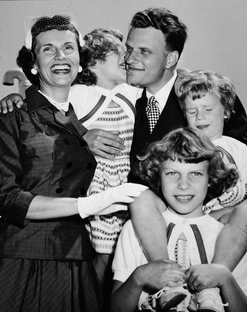 American evangelist Billy Graham embraces his family upon his return from his 'Crusade for Christ' tour, New York, New York, mid 1950s. Clockwise from left: Chinese-born wife Ruth, daughter Anne, Graham, daughter Ruth (Bunny), and daughter Virginia.
