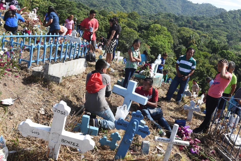 People visit the graves of their loved ones, during the commemoration of the day of the dead at a cemetery in Panchimalco, El Salvador on November 2, 2016.