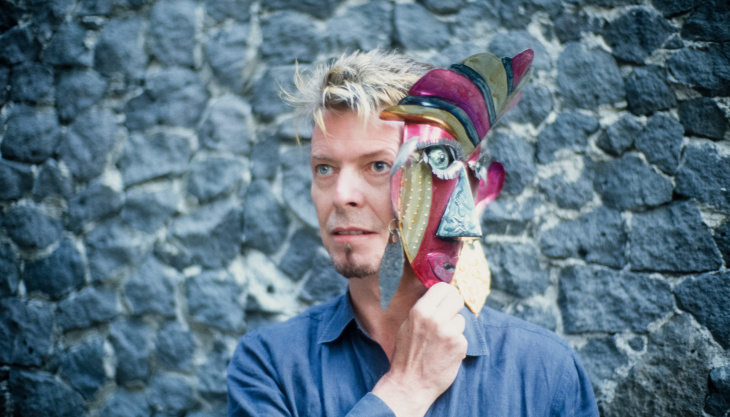 David Bowie holds a foil mask up to his face at Frida Kahlo's Blue House in Mexico in 1997.