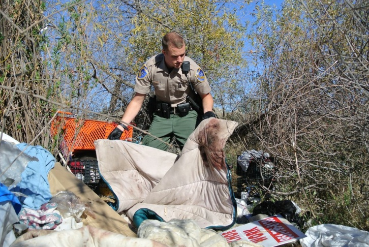 California Department of Fish And Wildlife Officer Nick Molsberry examines a homeless encampment in Perris, where a mountain lion is suspected of having attacked a 50-year-old man.