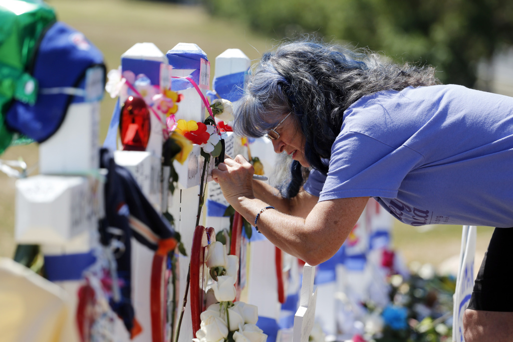 Michelle writes an inscription on a cross dedicated to the youngest victim, Veronica Moser Sullivan, at a temporary memorial of near the theater where 12 people were killed last year in Aurora, Colo., on Saturday, July 20, 2013. Coloradans marked the one-year anniversary of the Aurora movie theater massacre with a city-sponsored