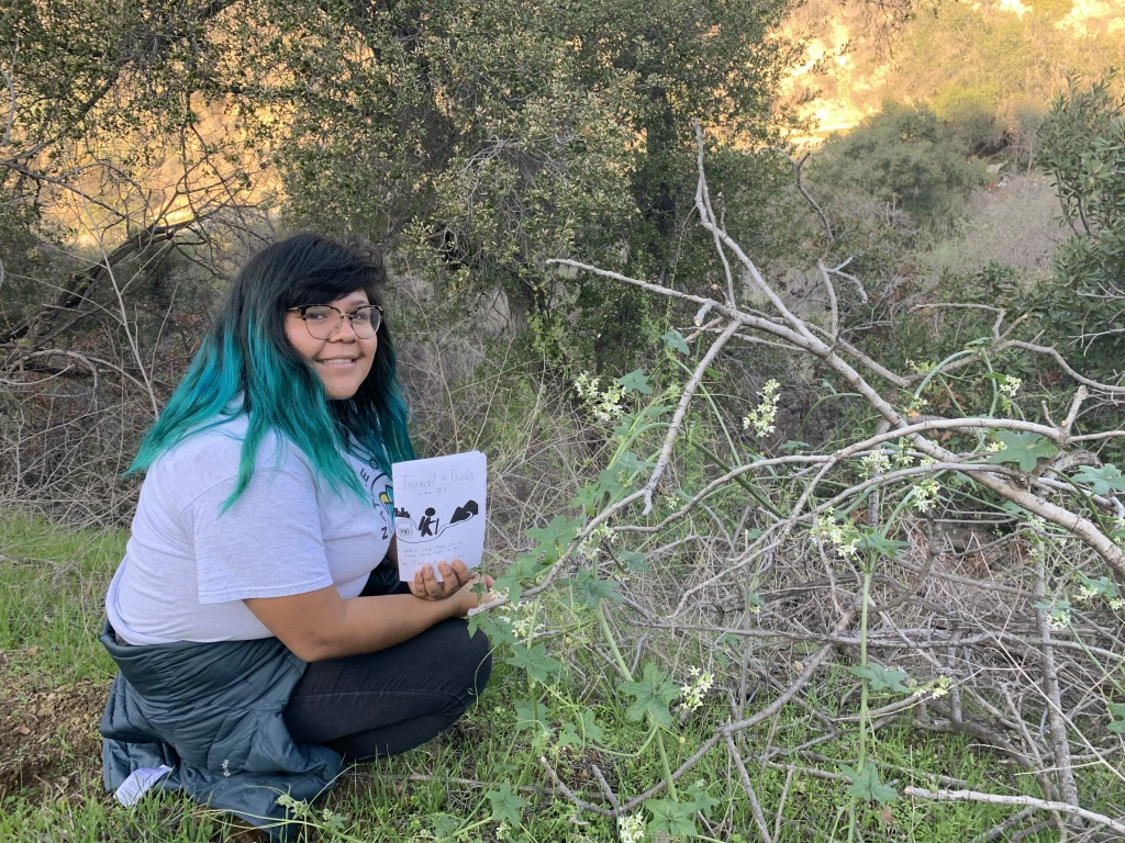 818Hikes co-founder Araceli Hernandez hold up her self-published zine with info on how to access trails in L.A.
