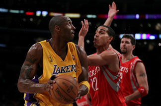 Kobe Bryant #24 of the Los Angeles Lakers looks to move the ball against Kevin Martin #12 of the Houston Rockets during their opening night game at Staples Center on October 26, 2010 in Los Angeles.