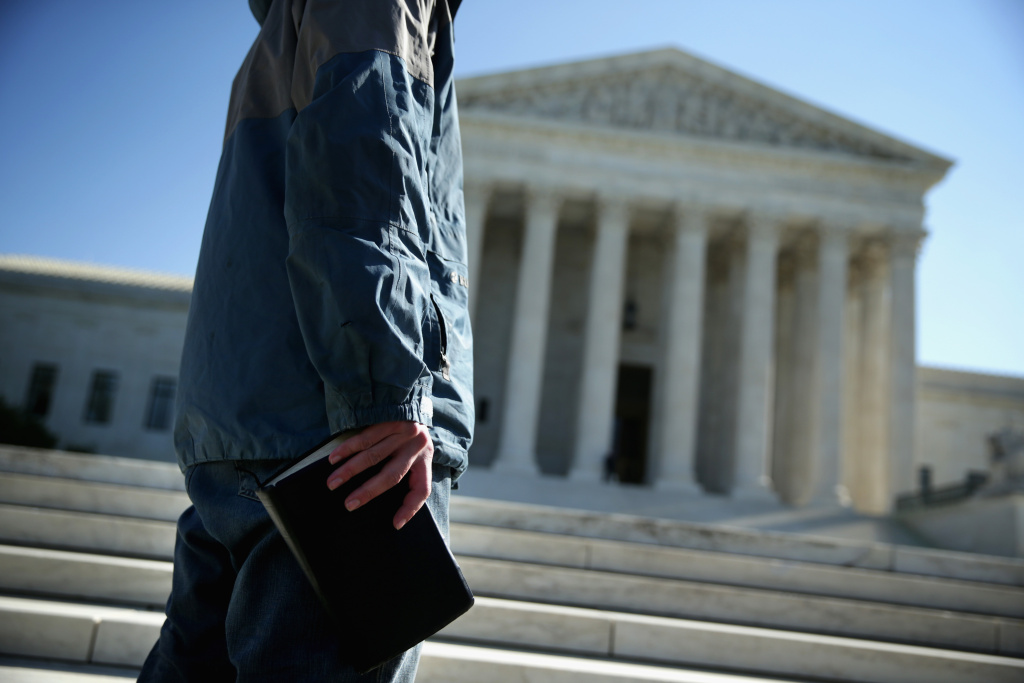 A conservative protester holds a bible as he participates in a prayer meeting in front of the U.S. Supreme Court Oct. 6, 2014 in Washington, DC. The Supreme Court announced that it will not hear the five pending same-sex marriage cases, paving the way for gay and lesbian marriage in 11 more states.