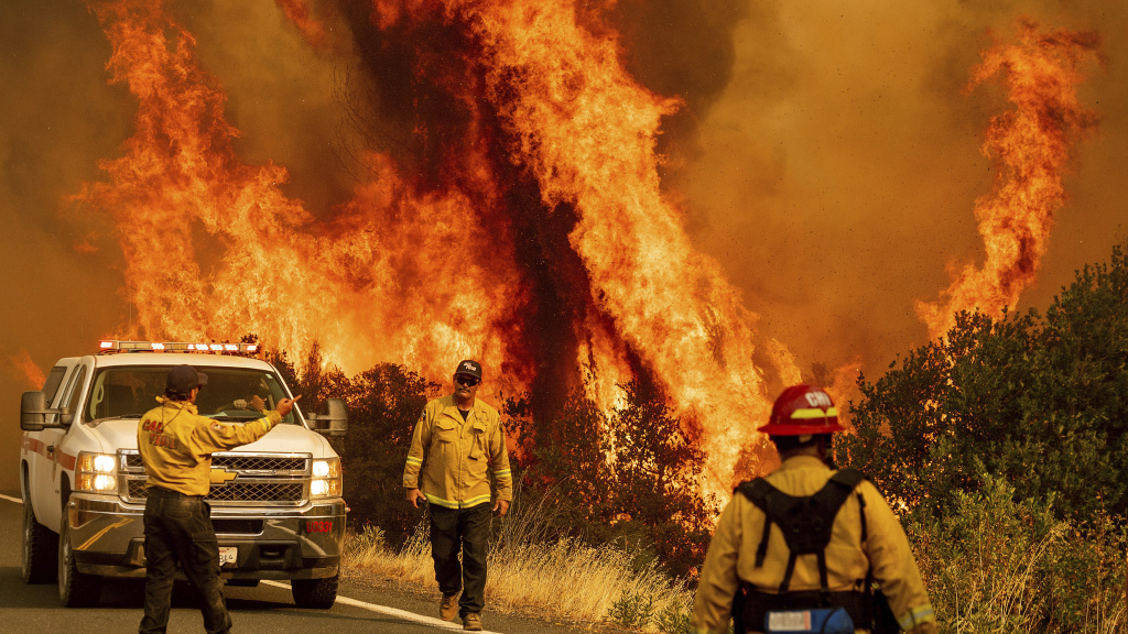 Flames from a fire in the LNU Lightning Complex leap above Butts Canyon Road on Sunday as firefighters work to contain the blaze in Lake County, Calif.