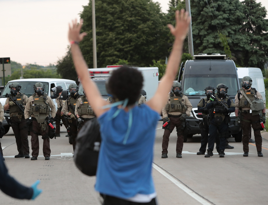 A demonstrator holds her hands up in front of police while protesting against the death of George Floyd, on May 31, 2020 in Minneapolis, Minnesota.