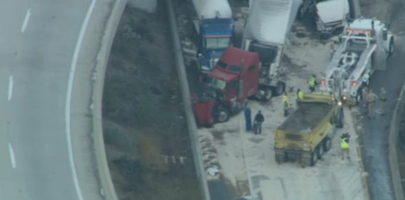 Crews work to clean up an accident involving nine big rigs on southbound Interstate 5 at the truck bypass tunnel at Newhall Pass north of Los Angeles early Tuesday morning.