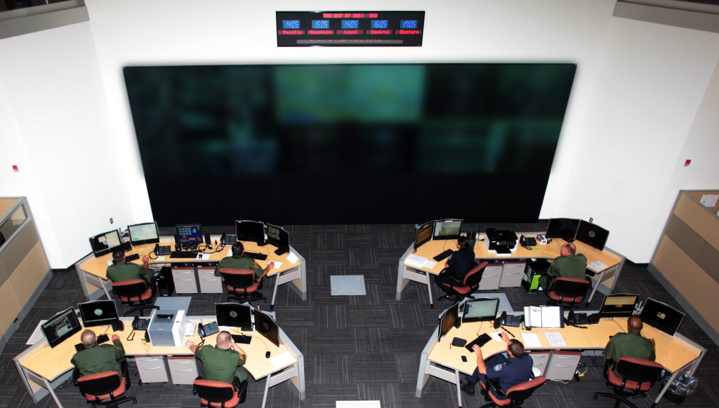 Agents at the Joint Intelligence and Operations Coordination Center in Tucson. The content of the video display screens have been blurred for security reasons.