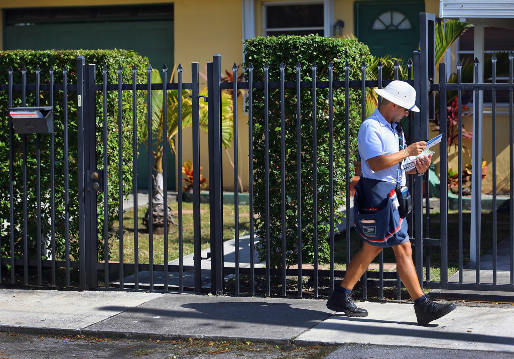 A mailman for the U.S. Postal Service delivers mail in Miami, Florida. The U.S. Postal Service recently reported a record annual yearly loss of $15.9 billion. The USPS plans to stop delivering mail on Saturdays but continue to deliver packages six days a week under a plan intended at saving about $2 billion annually,