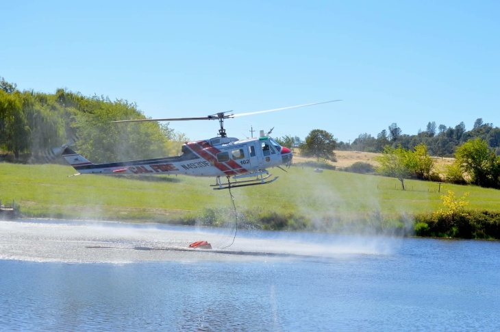A CalFire helicopter carries a bucket of water with smoke from the Clover Fire in the background. The helicopter is leaving a pond and about to fly over the photographer's home.