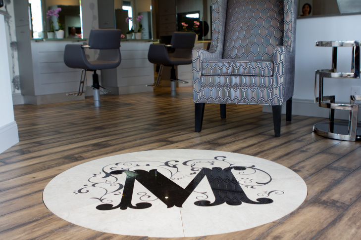 The new logo in front of the door at the newly redesigned Salon Meritage which is scheduled to open Tuesday, November 20, 2012 in Seal Beach, Calif. The salon closed after a deadly shooting in October 2011 in which a gunman killed seven people in the salon and one in the parking lot.