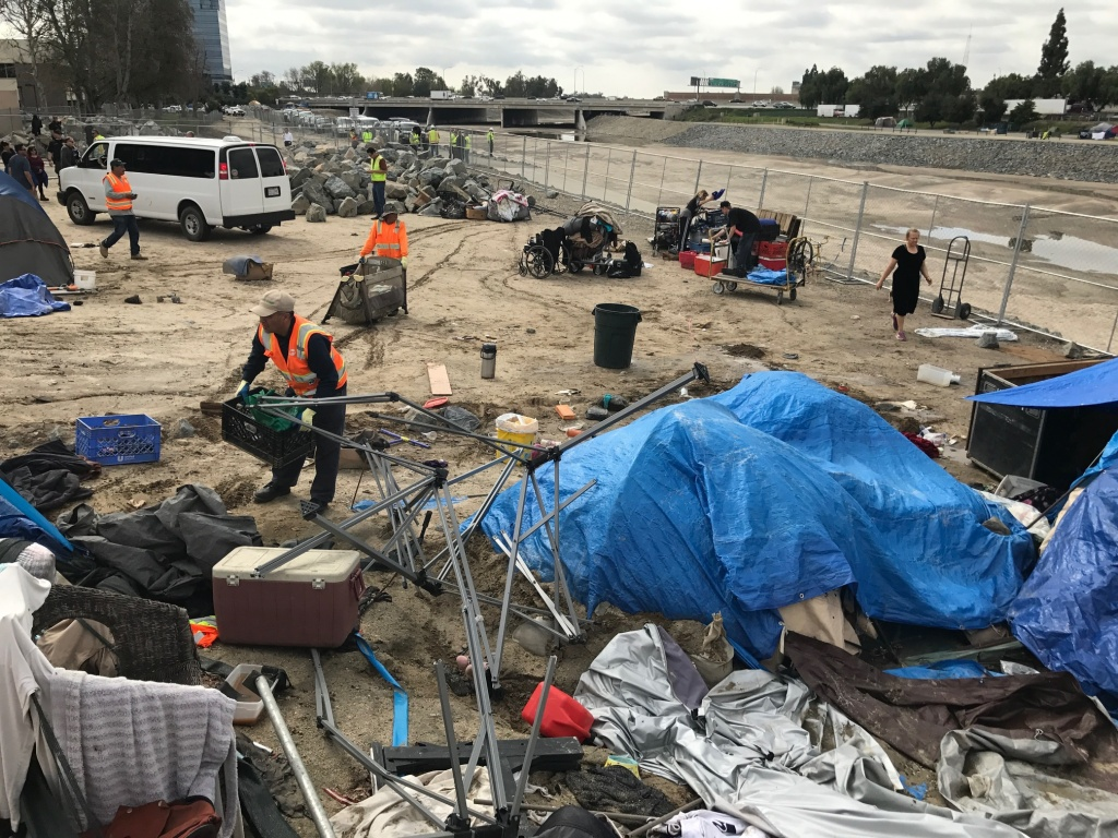Orange County workers help a homeless woman dismantle her camp off Chapman Avenue along the Santa Ana River. The county plans to remove some 250 people living along the river to clear the space to store riprap and sand.