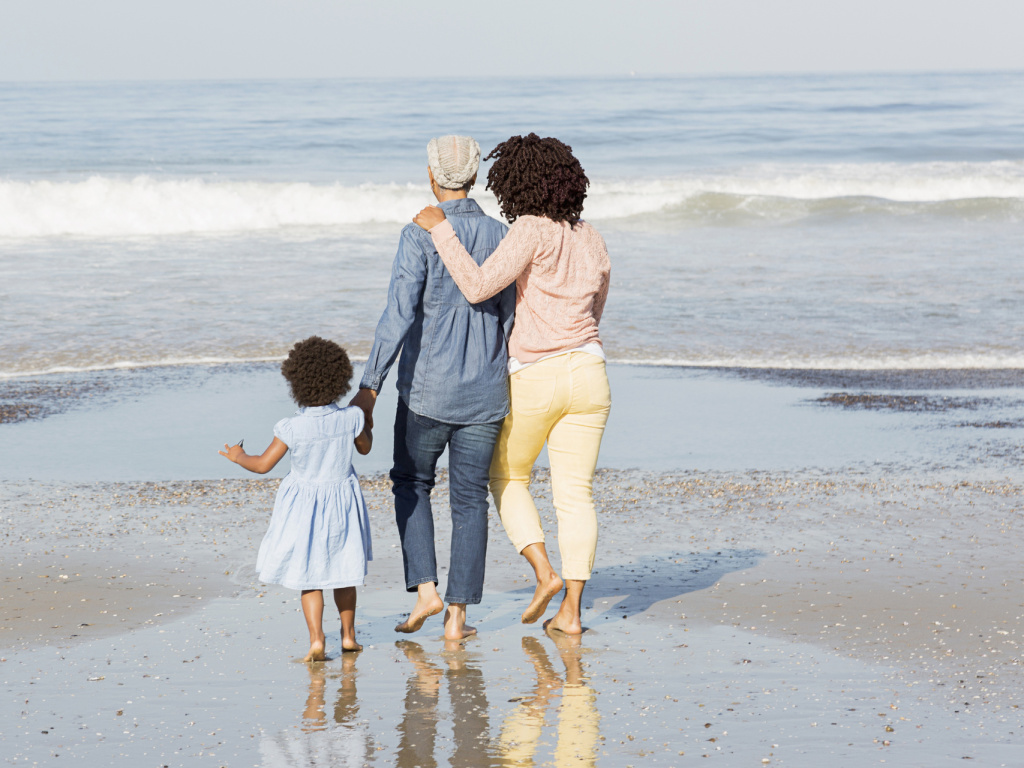 Two parents walking with their child on the beach