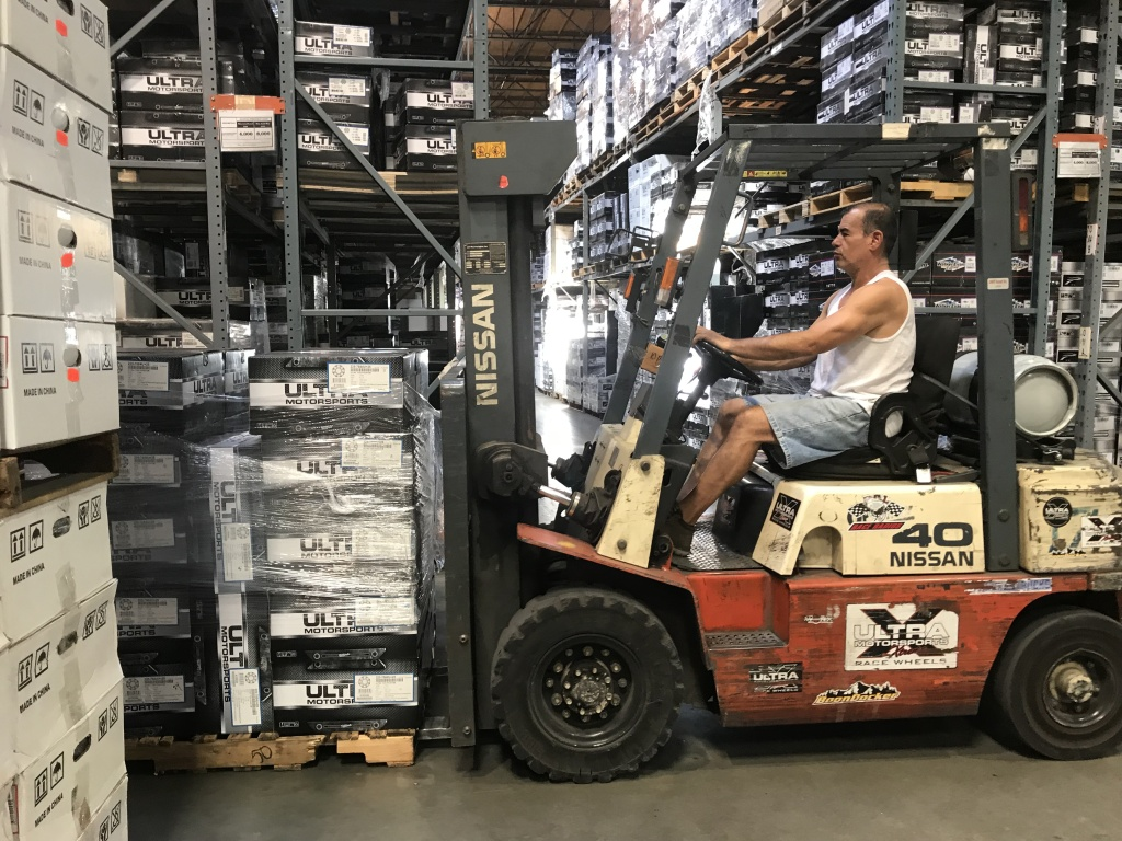 A forklift driver moves boxes of wheels in the warehouse of Fullerton-based company Ultra Wheel, Sept. 20, 2018.