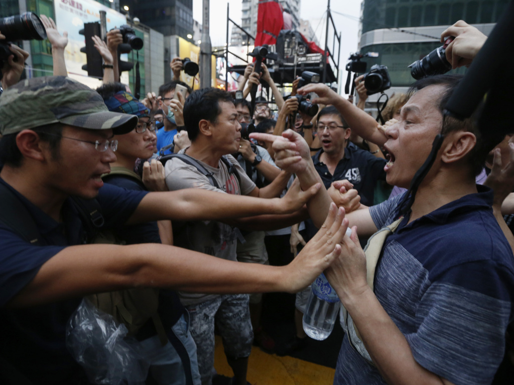 Pro-democracy protesters (left) stop an anti-Occupy Central protester from going near their tent on a main street at Hong Kong's Mongkok shopping district on Friday.