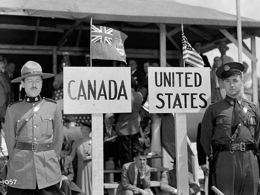A Royal Canadian Mounted Police officer stands in front of a sign marked