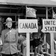 "A Royal Canadian Mounted Police officer stands in front of a sign marked ""Canada,"" beside an American state trooper."