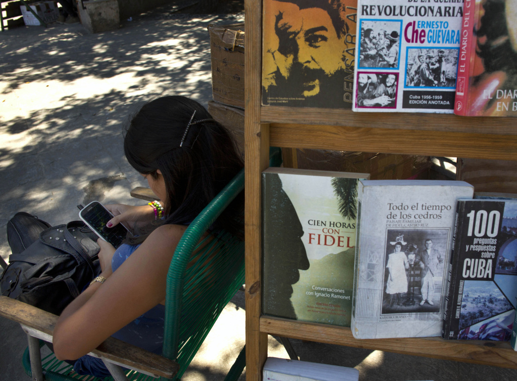 A book street vendor passes the time on her smart phone as she waits for customers in Havana, Cuba, on Tuesday. The Obama administration secretly financed a social network in Cuba to stir political unrest.