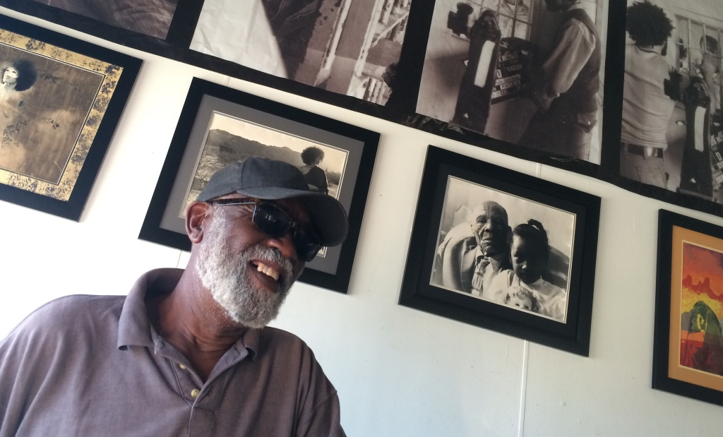 Ben Caldwell, a key figure in the L.A. Rebellion black cinema movement in the 1970s, at the KAOS Network studio in Leimert Park. He stands before photographs he took during that era.