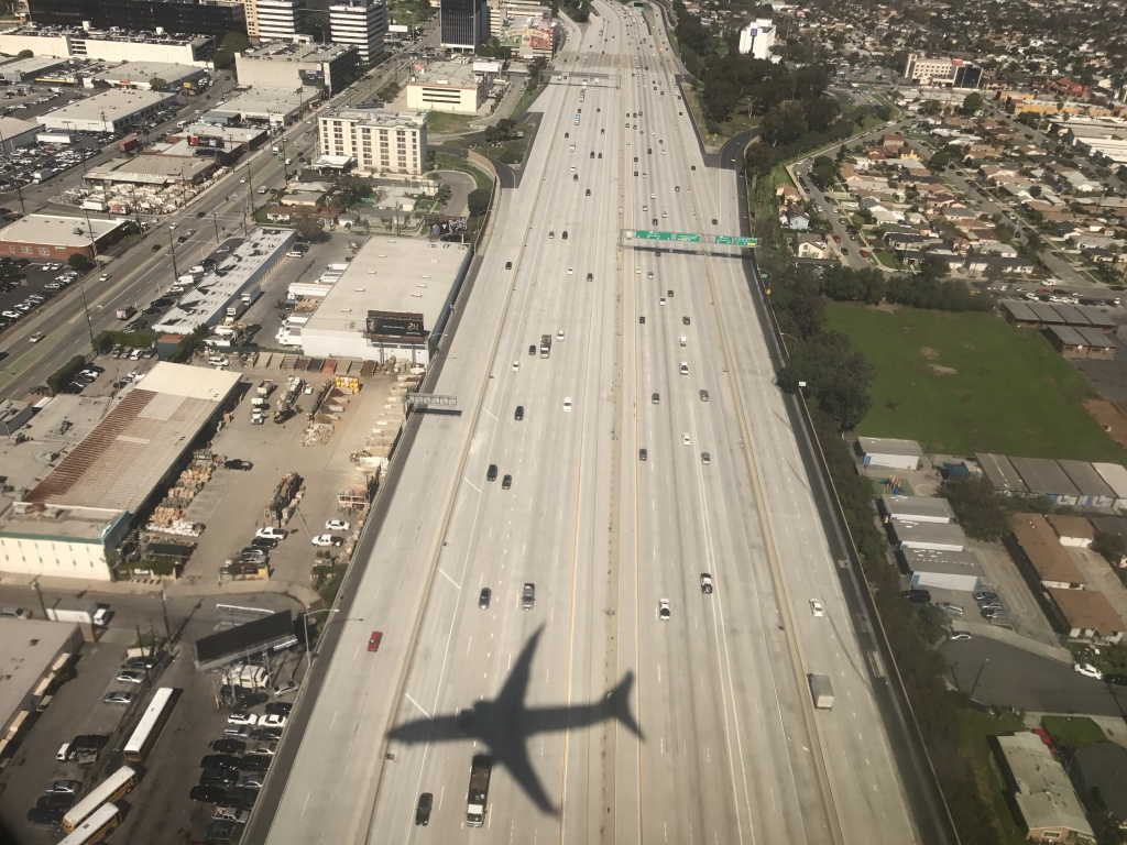 An airplane heads for LAX. Expansion plans at the airport are helping drive eminent domain plans for the Manchester Square neighborhood next door.