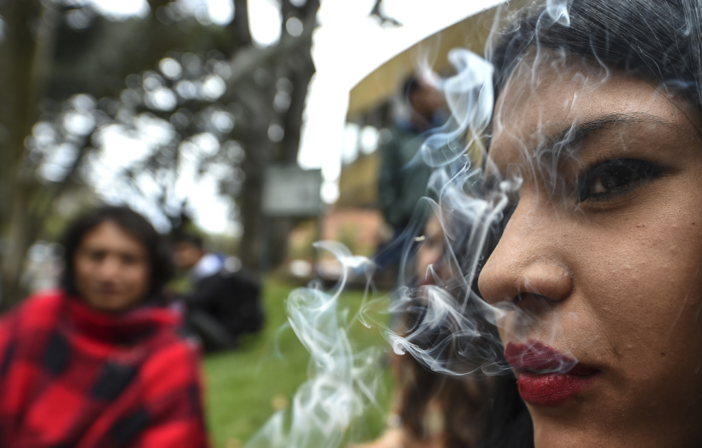 "An activist smokes a joint during a protest in Bogota, Colombia under the motto ""No vamos a pagar, lo vamos a pegar"" ('We are not going to pay for it, we are going to get the kick out of it""). She and others were protesting against fines for smoking marijuana on August 1, 2017."