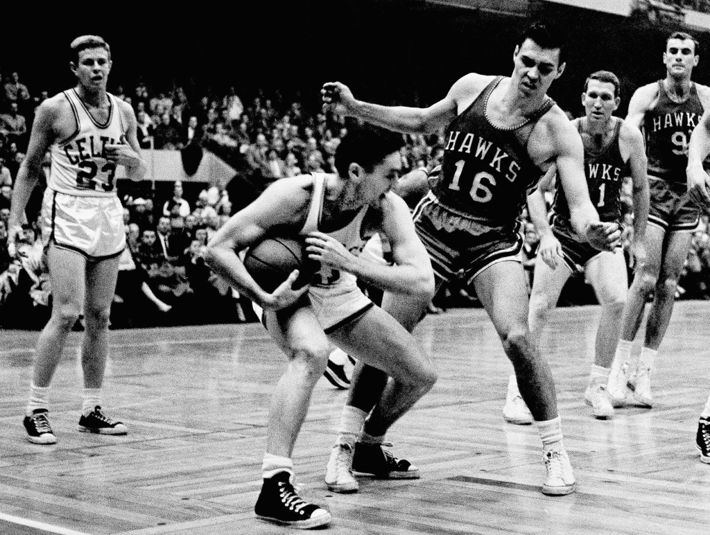 FILE - In this March 30, 1958, file photo, Boston Celtics'  Bill Sharman holds the ball as St. Louis Hawks' Cliff Hagan (16), defends, during the second half of an NBA Finals basketball game in Boston. Sharman, the Hall of Famer who won NBA titles as a player for the Boston Celtics and a coach for the Los Angeles Lakers, has died. He was 87.  Sharman died Friday, Oct. 25, 2013, at his home in Redondo Beach, the Lakers announced.