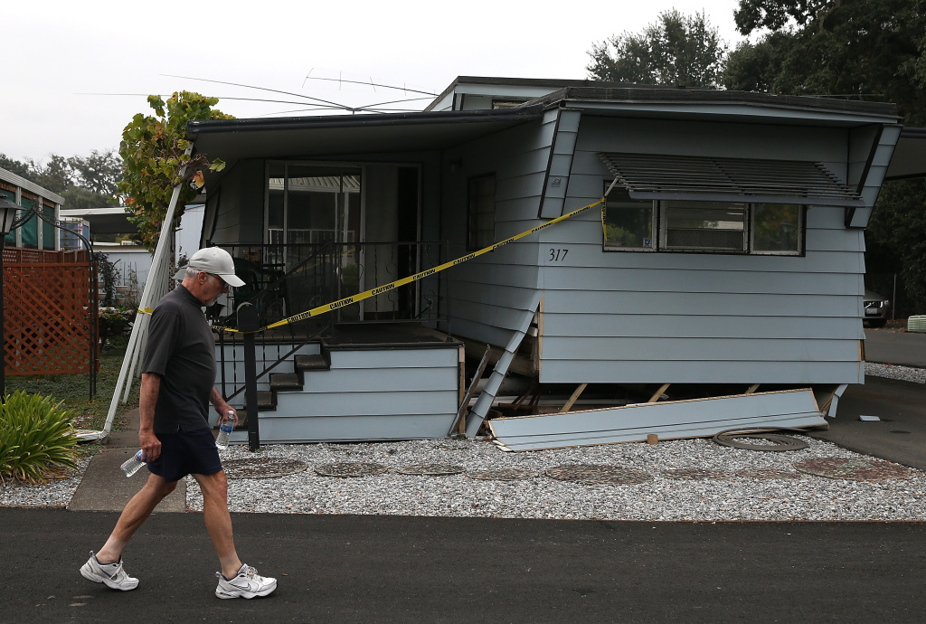 A pedestrian walks by a mobile home that shifted off of its foundation at a mobile home park following a reported 6.0 earthquake on August 24, 2014 in Napa, California.