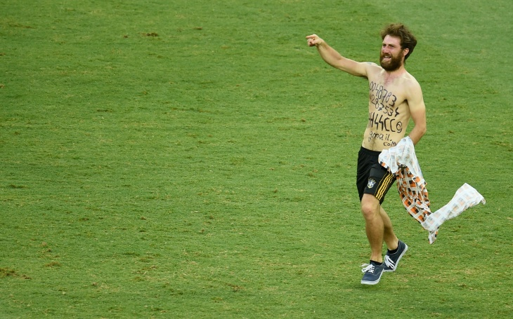 A pitch invader gestures during a Group G football match between Germany and Ghana at the Castelao Stadium in Fortaleza during the 2014 FIFA World Cup on June 21, 2014. The game ended with a draw 2-2.