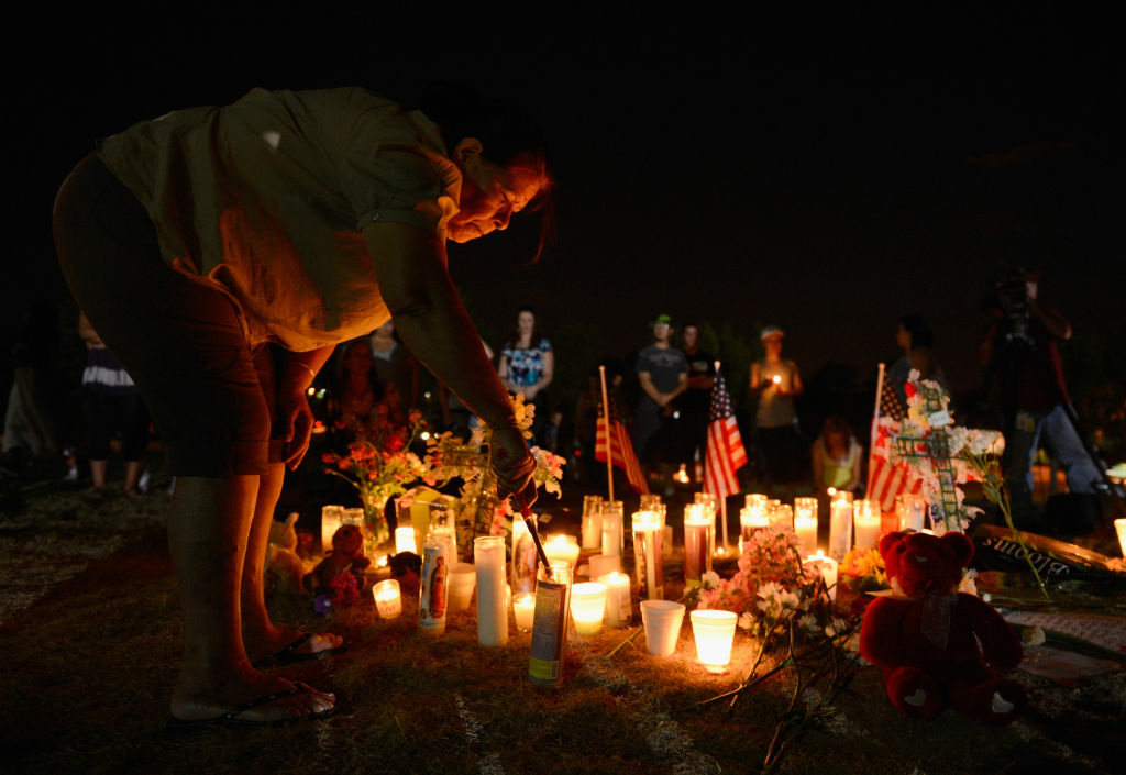 A woman lights candles at a makeshift memorial during a vigil for victims of the Century 16 movie theatre where a gunmen attacked movie goers during an early morning screening of the new Batman movie