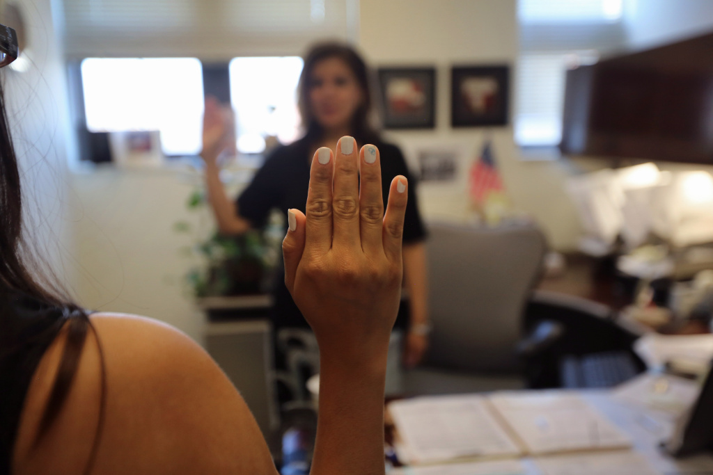 A Colombian immigrant swears to tell the truth before taking her oral citizenship test at the U.S. Citizenship and Immigration Services (USCIS) office.