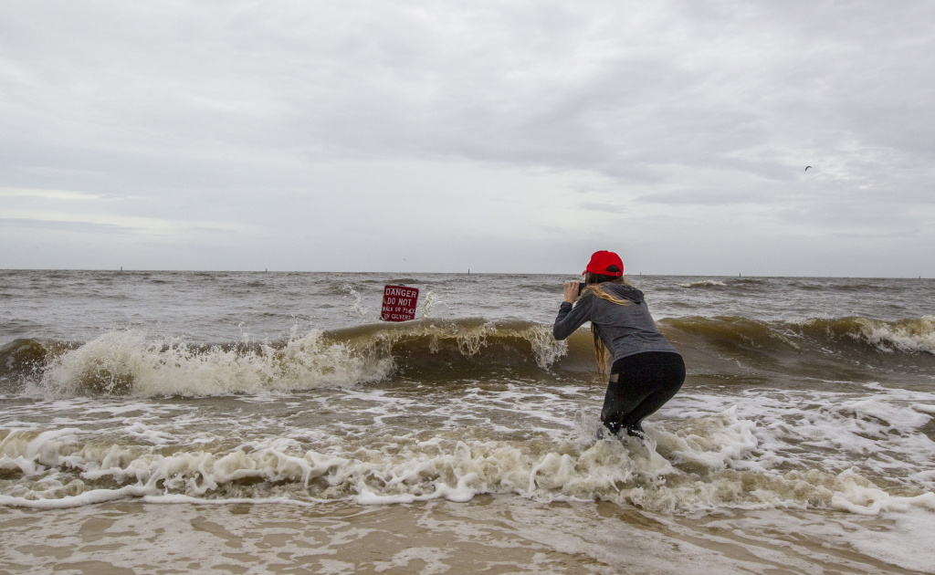 Hannah Jacole Powell-Yost takes photos of a danger sign in the Gulf surf in Gulfport, Mississippi as Hurricane Nate approaches the Gulf Coast on Saturday, October 7, 2017.
