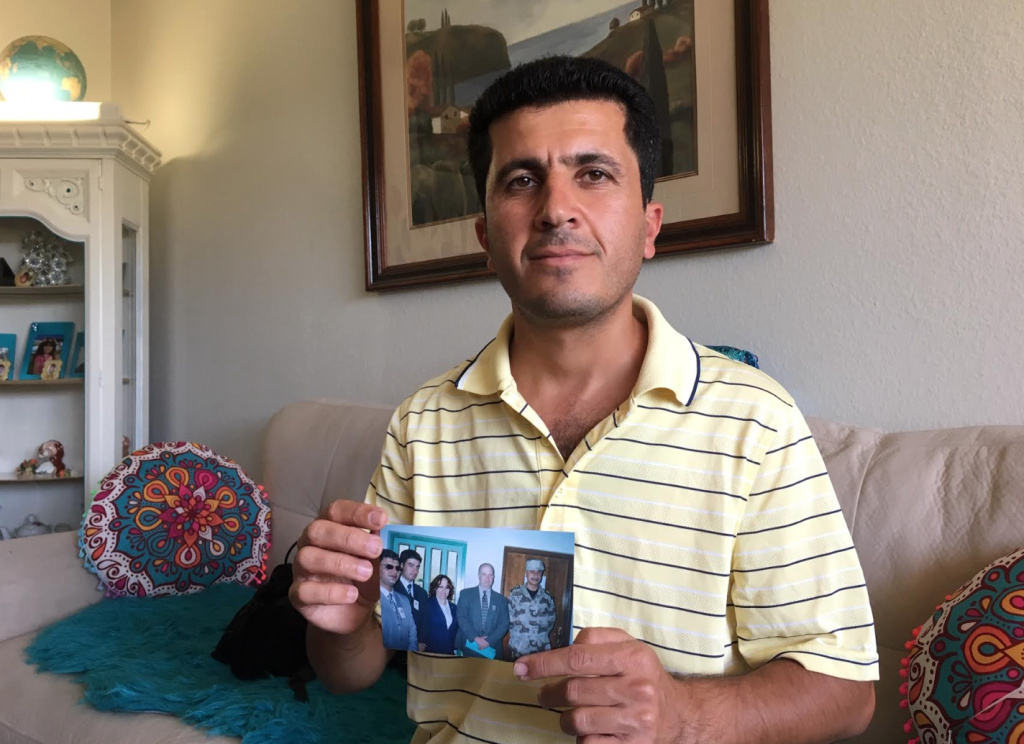 Kewa Sharif holds a photo of colleagues during the Iraq war, including his longtime friend who has been unable to follow him to the U.S. as a refugee. Both worked IT jobs supporting the U.S. military during the war.
