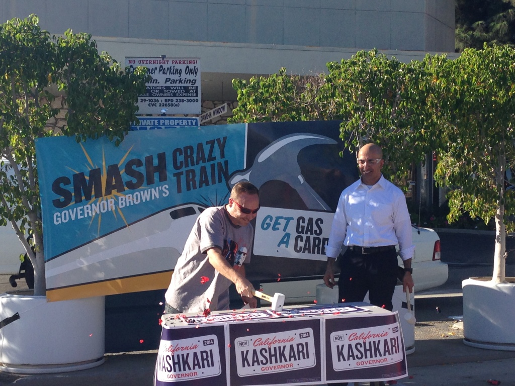 Republican Neel Kashkari looks on as a supporter breaks apart a plastic toy train in exchange for a $25 gas card.