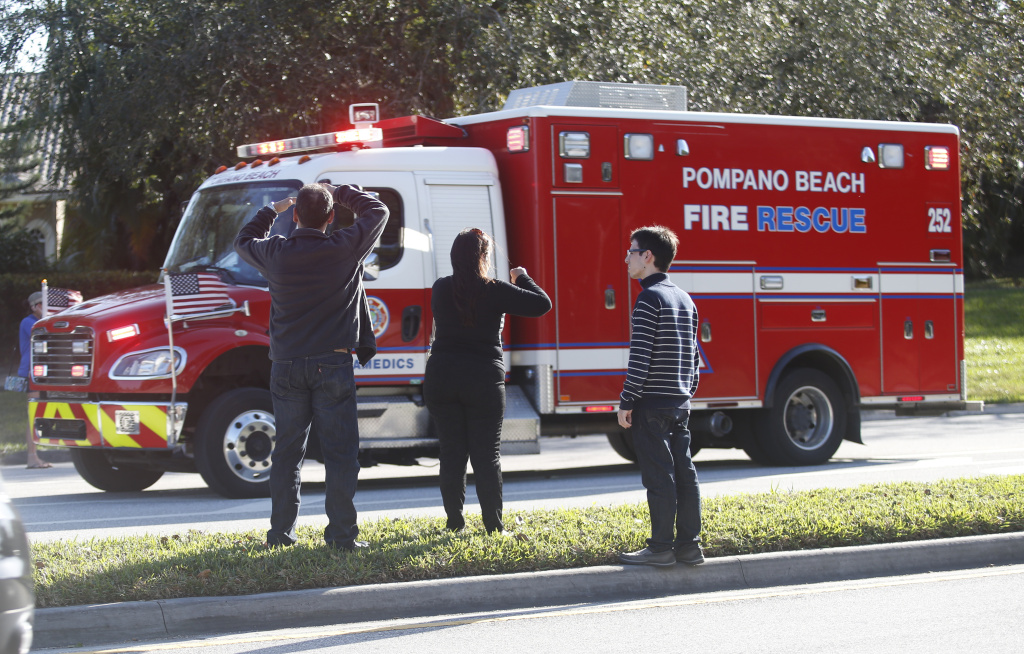 Anxious family members watch a rescue vehicle pass by, Wednesday, Feb. 14, 2018, in Parkland, Fla. A shooting at Marjory Stoneman Douglas High School school sent students rushing into the streets as SWAT team members swarmed in and locked down the building.