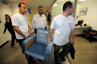 Majed Abdulfattah (L), Basem al Baz (C) and Ahmad Dari (R) carry a symbolic Palestinian seat to a meeting with United Nations General Assembly President Nassir Abdulaziz Al-Nasser September 15, 2011 at UN headquarters in New York ahead of preparations to request UN membership for Palestine.