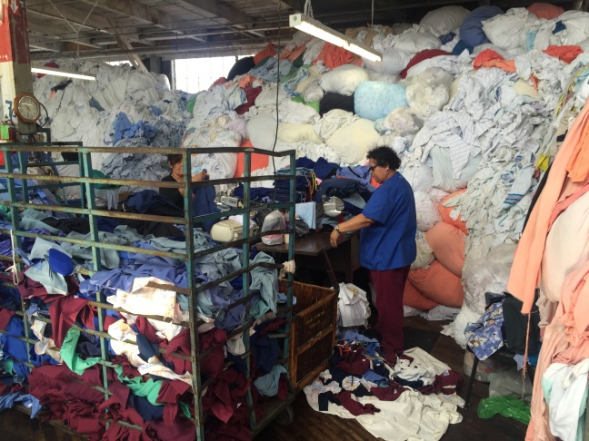 Two workers at A and A Wiping Cloth cut old linens into rags for use in janitorial and automotive services.