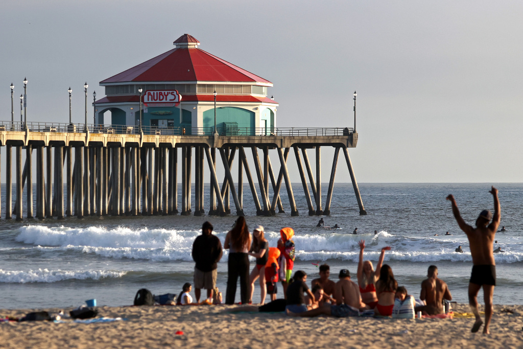 People gather at the beach in front of the pier on April 30, 2020 in Huntington Beach, California.