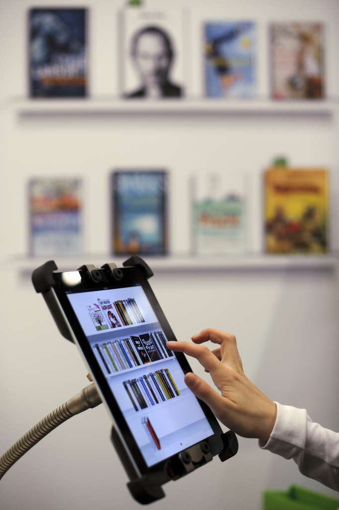 A fair goer tries out Deutsche Telekom's PagePlace eBook reader app on an Apple iPad at the Leipzig Book Fair on March 15, 2012