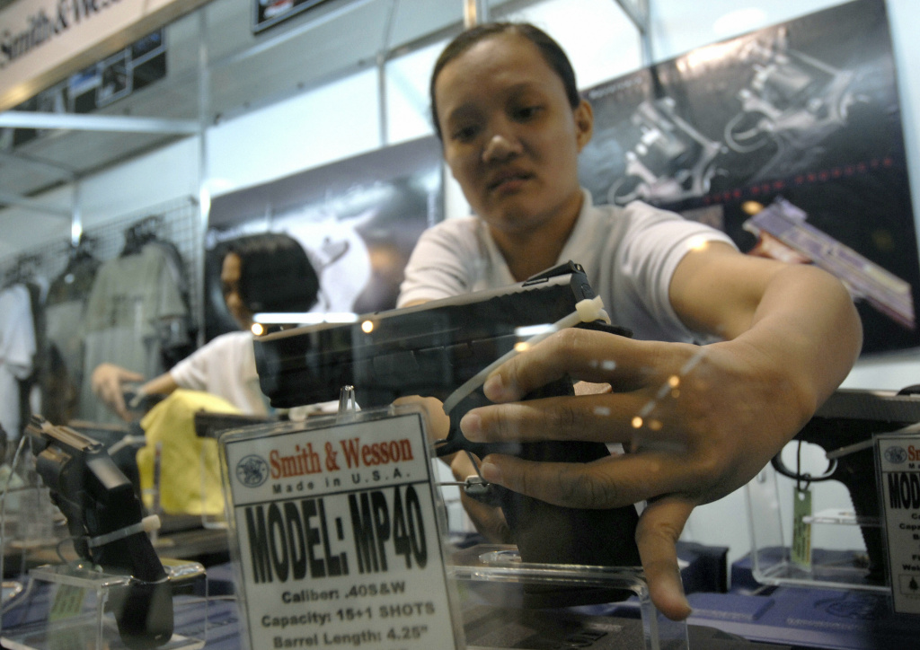 A gun store attendant places a US-made Smith and Wesson MP40 handgun into its cradle during the first day of an annual defense and sporting arms show in a commercial center in Manila on July 17, 2008. The company said on Thursday that it will stop selling its semi-automatic pistols in California rather than comply with a new gun control law there.