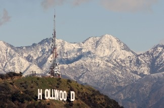 The Hollywood sign and the undeveloped land that surrounds it are seen against the snow-covered San Gabriel Mountains.
