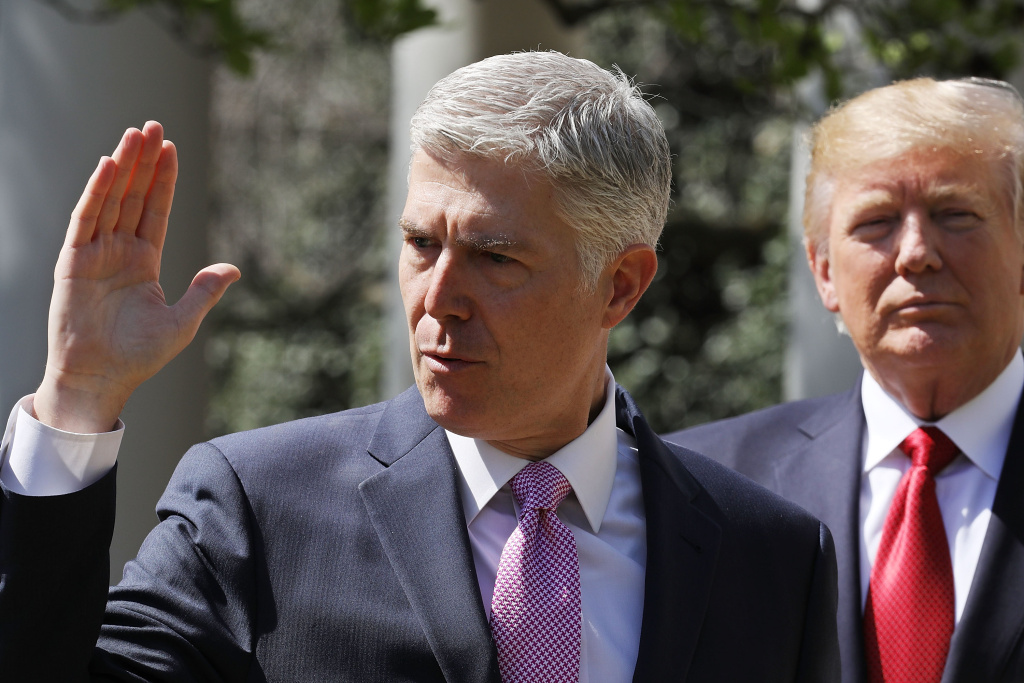 WASHINGTON, DC - APRIL 10:  U.S. Supreme Court Associate Justice Judge Neil Gorsuch (L) takes the judicial oath as President Donald Trump looks on during a ceremony in the Rose Garden.
