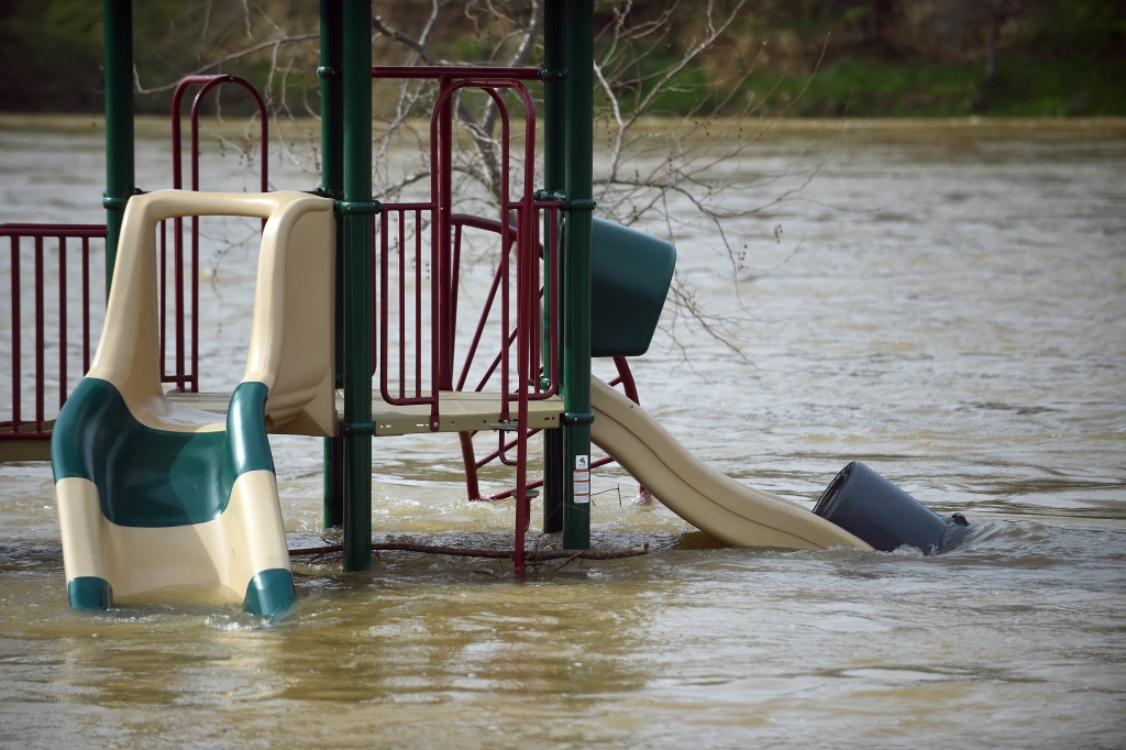 A swing is seen partially submerged in flowing water at Riverbend Park in Oroville, California on February 13, 2017.