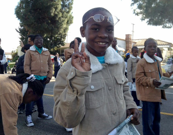 A member of Haiti's Miracle Choir flashes a peace sign as he marches in the annual Martin Luther King Jr. parade in L.A.