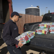 Volunteer firefighter, Christian Avalos loads bottled water into the bed of a truck for resident Donna Johnson to distribute as water wells supplying hundreds of residents remain dry in the fourth year of worsening drought on February 11, 2015 in East Porterville, California.