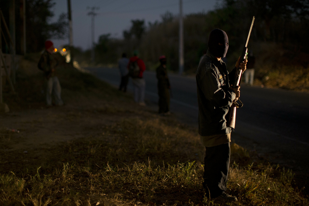 An armed and masked man guards a roadblock at the entrance to the community of Cruz Quemada, near Ayutla, early Saturday, Jan. 19, 2013. Hundreds of  men in the southern Mexico state of Guerrero have taken up arms to defend their villages against drug gangs, a vigilante movement born of frustration at extortion, killings and kidnappings in a region wracked by violence.