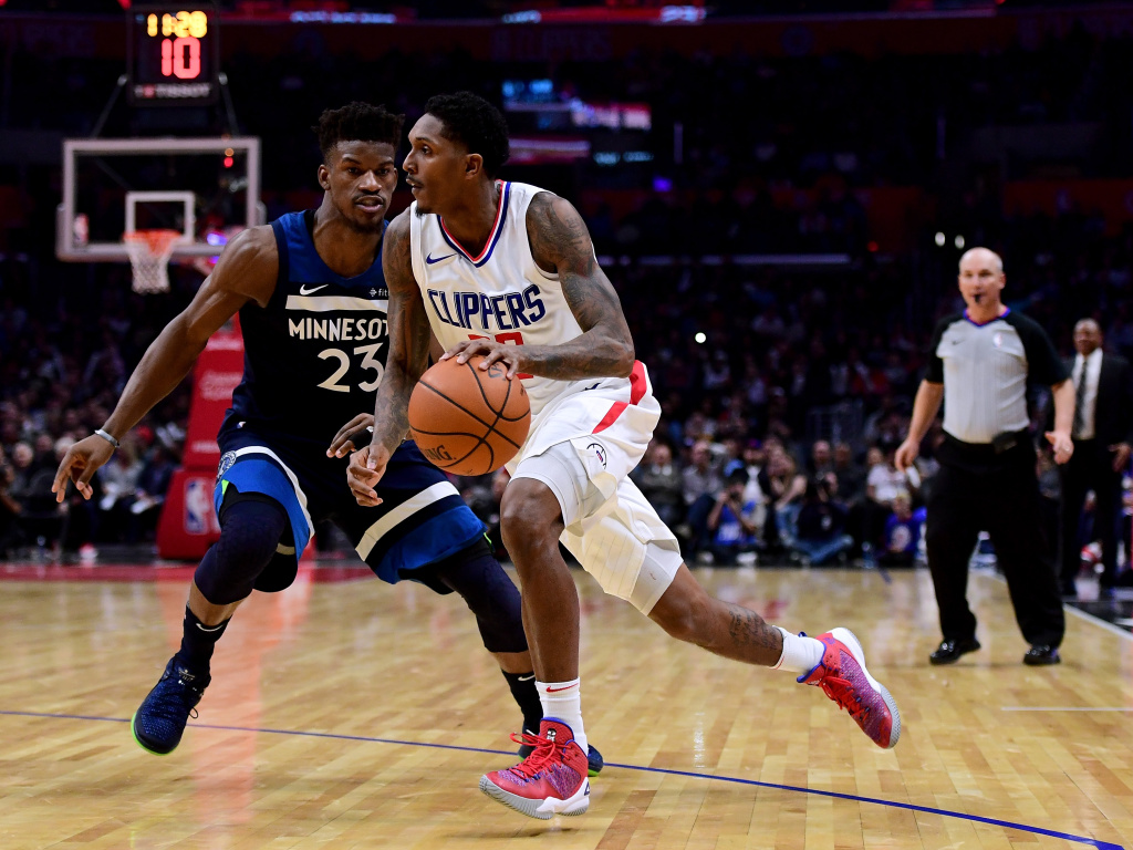 Lou Williams #23 of the LA Clippers drives to the basket on Jimmy Butler #23 of the Minnesota Timberwolves during a 113-107 Timberwolves win at Staples Center on December 6, 2017 in Los Angeles, California.