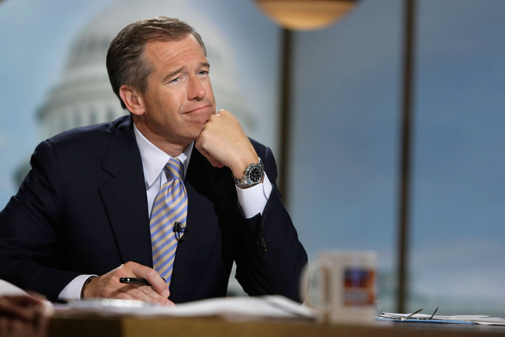 Moderator Brian Williams watches a video which pays tribute to late moderator Tim Russert during a taping of