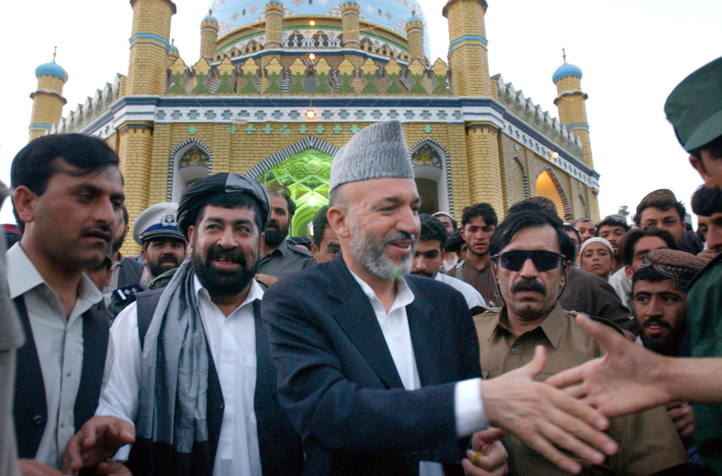 Afghan President Hamid Karzai, center, shakes hands with a supporter as he leaves the Mirwaise Nikah shrine (the tomb of a Pashtun tribal leader) in Kandahar, Afghanistan on Friday, Aug. 2, 2002. On the President's right is Gul Agha, governor of Kandahar, and on the president's left is the Afghan Chief of Intelligence, Haji Gulalai.