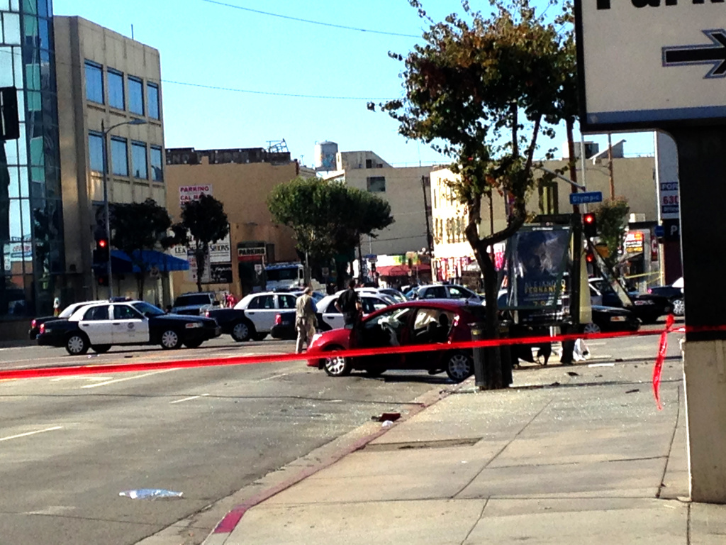 Detectives examine the scene of a crash and officer involved shooting Saturday in downtown Los Angeles. Police say Brian Newt Beaird, 51, of Oceanside led them on an hour long chase through city streets before slamming into a passing car, then attempting to escape.